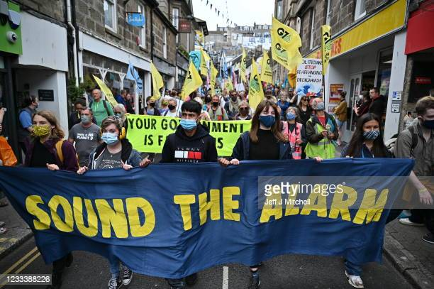 """Extinction Rebellion activists take part in the """"Sound The Alarm"""" march during the G7 summit in Cornwall on June 11, 2021 in St Ives, Cornwall,..."""