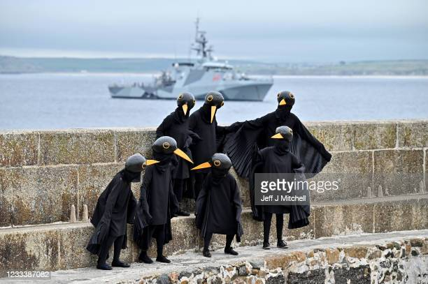 """Extinction Rebellion 'Blackbirds XR' activists stage a """"Wake-up Call"""" theatrical action during the G7 summit in Cornwall on June 11, 2021 in St Ives,..."""