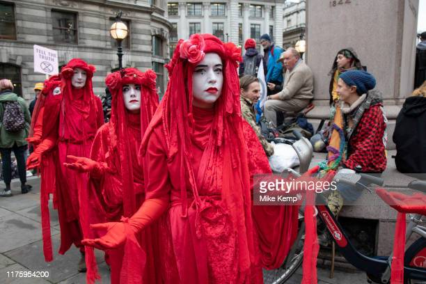 Extinction Rebellion climate change activist performance art troupe the 'Red Rebel Brigade' wearing bright red costumes march silently at Bank in the...