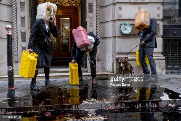 Extinction Rebellion Climate Change activists dressed in City suits, vomit 'oil' outside the Baltic Exchange, home to the International Chamber of...