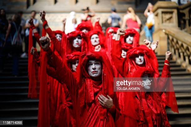 TOPSHOT Extinction Rebellion climate change activists in red costume attend a mass die in in the main hall of the Natural History Museum in London on...