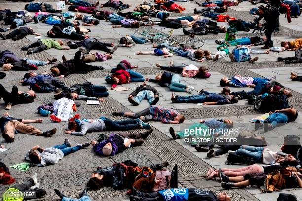 Extinction Rebellion climate change activists lie on the floor to symbolize a mass die at the Gendarmenmarkt square in Berlin on April 27 2019...