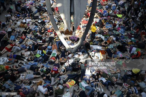 TOPSHOT Extinction Rebellion climate change activists perform a mass die in under the blue whale in the foyer of the Natural History Museum in London...