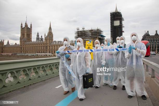 Extinction Rebellion crime scene investigators in white suits and masks walk over Westminster Bridge past the Houses of Parliament with climate crime...