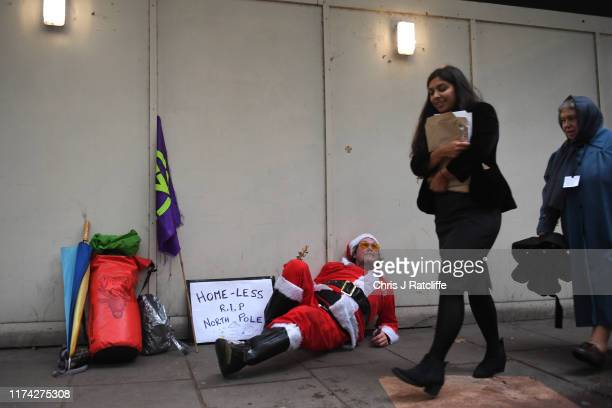 Extinction Rebellion demonstrator dressed as a homeless Sants protests on Millbank in Westminster on October 7 2019 in London England Climate change...