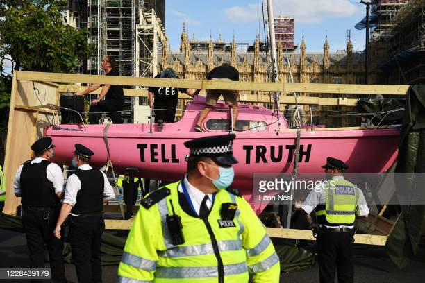 Extinction Rebellion demonstrators drive a vehicle carrying a pink boat into Parliament Square during a protest on September 10 2020 in London...