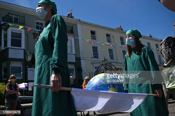 Extinction Rebellion environmental activists and supporters protest in the streets of Falmouth, Cornwall during the G7 summit on June 12, 2021.
