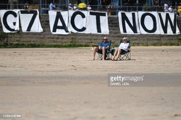 Extinction Rebellion environmental activists attach a banner calling on G7 leaders to act on climate change on the beach in St Ives, Cornwall during...