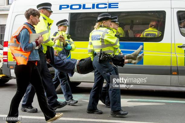 Extinction Rebellion environmental activists attempt to prevent police from removing their roadblocks at the end of Oxford Street around Marble Arch...