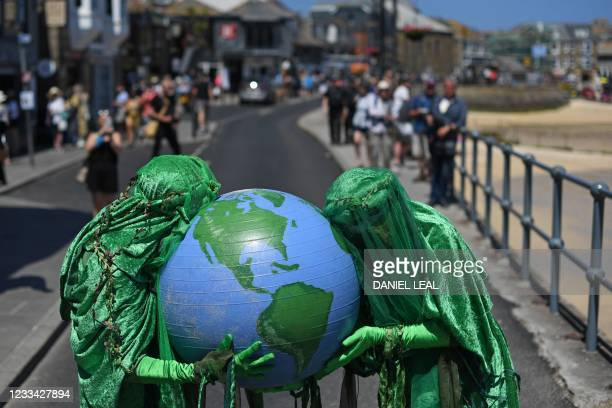Extinction Rebellion environmental activists do a performance as they protest in the streets of St Ives, Cornwall during the G7 summit on June 13,...