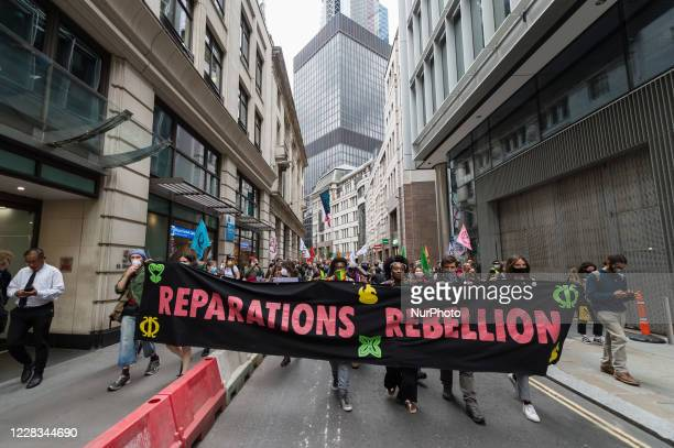 Extinction Rebellion environmental activists march through the City of London to protest against the companies and institutions that profited from...