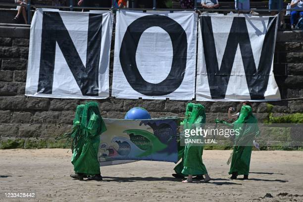 Extinction Rebellion environmental activists put on a performance as they protest on the beach in St Ives, Cornwall during the G7 summit on June 13,...