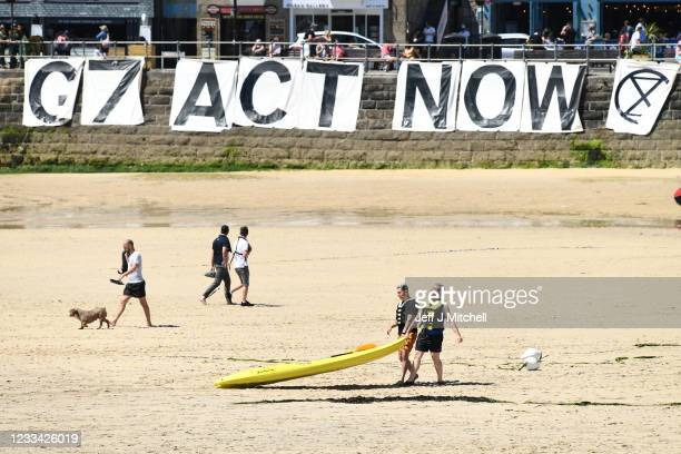 """Extinction Rebellion environmental activists stage a demonstration with a banner saying """"G7 Act Now"""" on the beach during the G7 summit on June 13,..."""