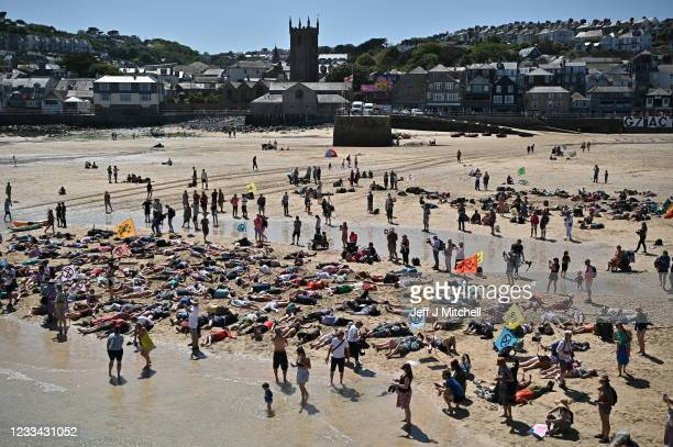Extinction Rebellion environmental activists stage a 'die-in' demonstration on the sand at the harbour during the G7 summit on June 13, 2021 in St...