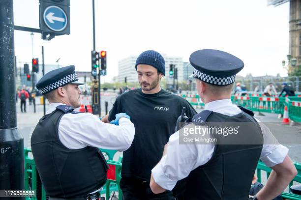 Extinction Rebellion environmental activists stopped and searched by police outside Westminster Underground station on their way to an action site...