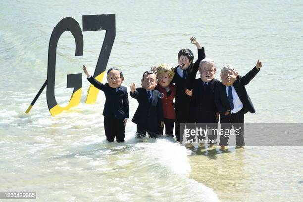 Extinction Rebellion environmental activists wearing masks of some of the G7 leaders, stage a demonstration during the G7 summit on June 13, 2021 in...