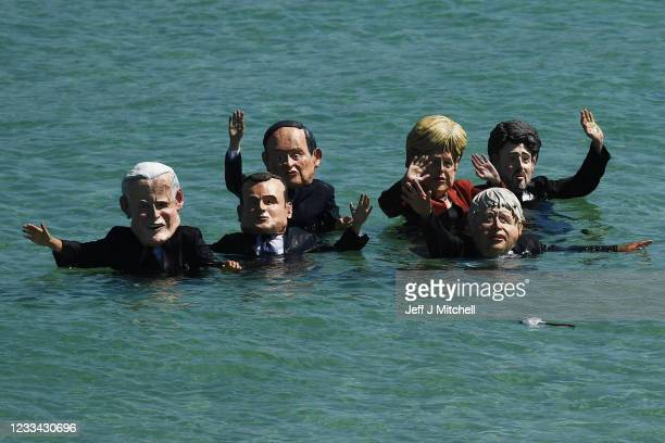Extinction Rebellion environmental activists wearing masks of some of the G7 leaders, stage a demonstration in the sea during the G7 summit on June...