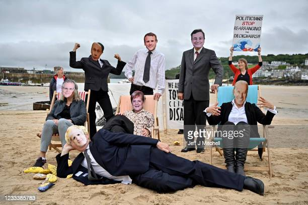 """Extinction Rebellion 'Money Rebellion' protesters stage a """"Stop Rearranging the Deckchairs"""" Titanic theatrical beach action during the G7 summit in..."""