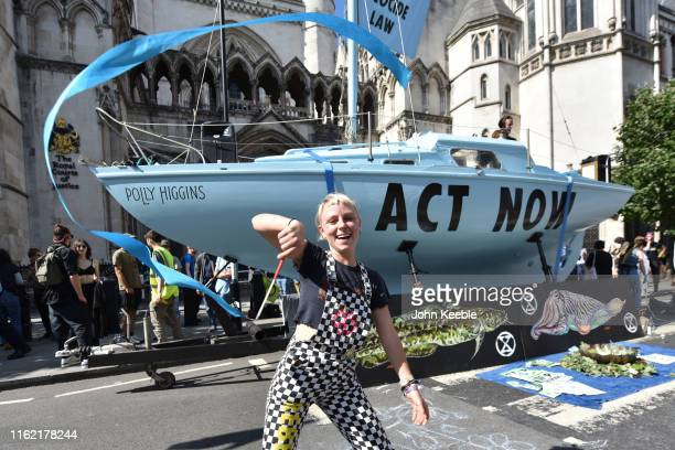 "Extinction Rebellion protester dances with ribbon in front of the blue boat called ""Polly Higgins"" outside the Royal Courts of Justice on the Strand..."