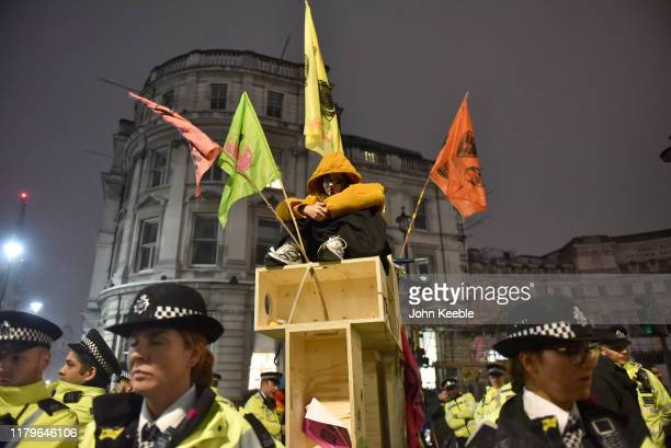 Extinction Rebellion protester is circled by police at Trafalgar Square on October 07 2019 in London England Climate change activists are gathering...