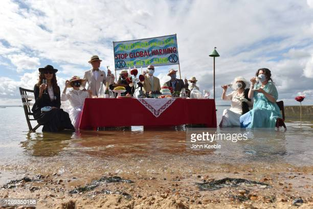 Extinction Rebellion protesters stage a Titanicthemed dinner party in the sea to illustrate the threat of rising sea levels on Chalkwell beach on...