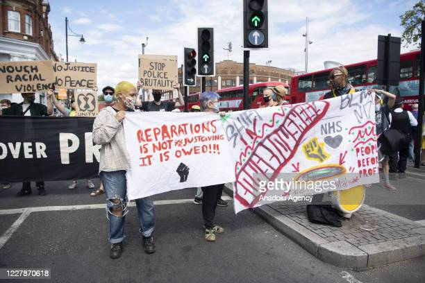 August 01: Extinction Rebellion protesters take part supporting Reparations March UK & Afrikan Emancipation Dayreclaim Brixton town centre in order...