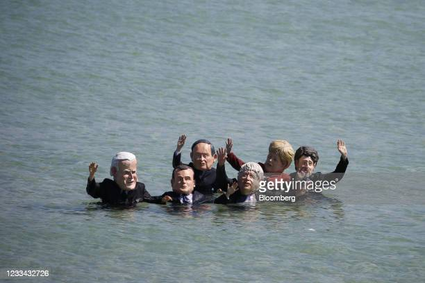 Extinction Rebellion protesters wearing masks depicting from left to right, U.S. President Joe Biden, Emmanuel Macron, France's president, Yoshihide...