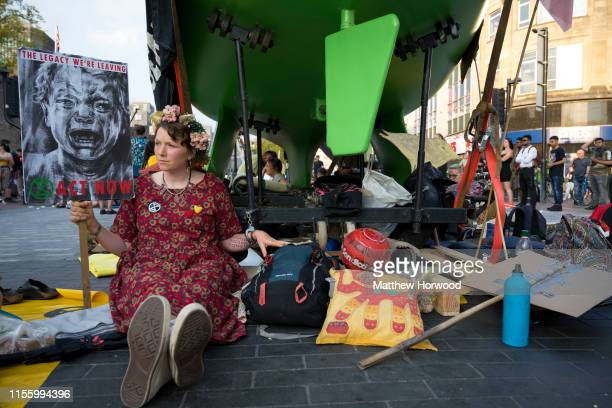 Extinction Rebellion protestor sits handcuffed to a boat on Duke Street outside Cardiff Castle as the environmental protest group ends day two of a...