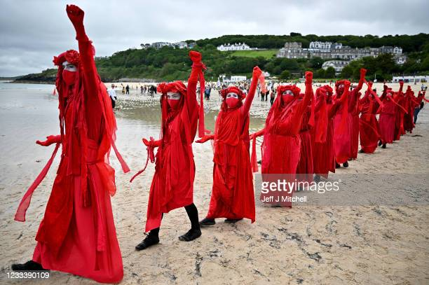 """Extinction Rebellion 'Red Rebels' activists take part in the """"Sound The Alarm"""" march during the G7 summit in Cornwall on June 11, 2021 in St Ives,..."""
