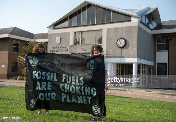 """Extinction Rebellion Southend protesters hold placards and banners as they pour fake oil down the throats of four """"victims"""" in protest outside the..."""
