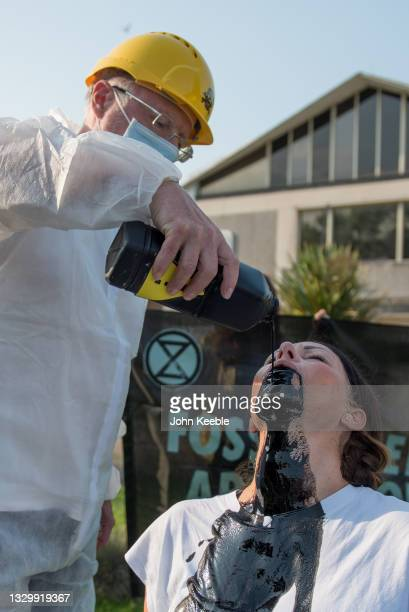 """Extinction Rebellion Southend protesters pour fake oil down the throats of four """"victims"""" in protest outside the Castle Point council offices on July..."""