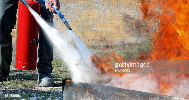extinguishing with powder type fire extinguisher - fire extinguisher stock photos and pictures