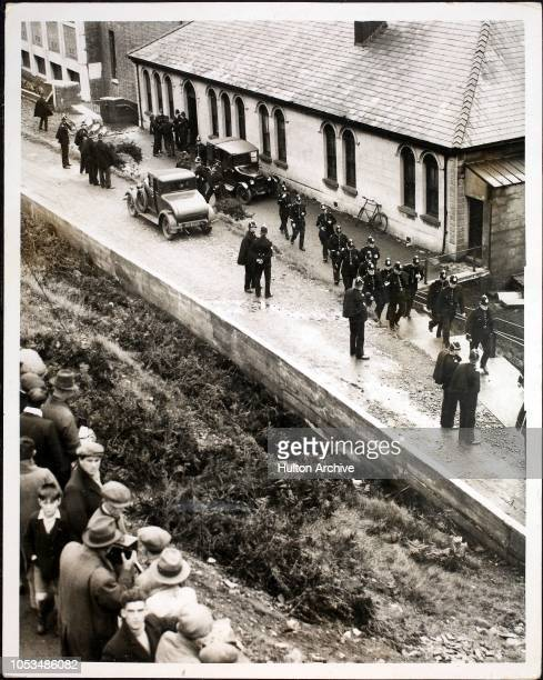Extra police officers forming a cordon round a colliery in Wyllie, South Wales, before the striking miners were brought up, 15th October 1935....