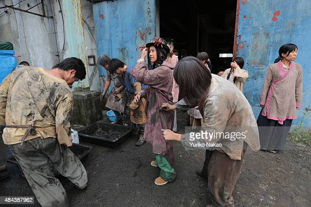 Extras for director Shinji Higuchi's film 'Attack on Titan' put mud on their costumes before filming on June 9 2014 in Takahagi Japan