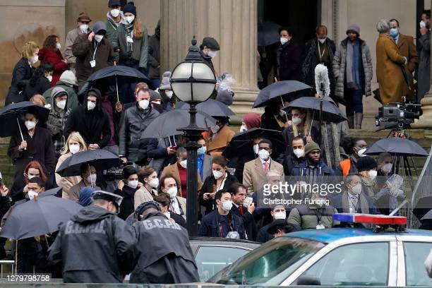 Extras in the filming of The Batman movie wear Covid-19 protective face masks between takes at St George's Hall on October 12, 2020 in Liverpool,...