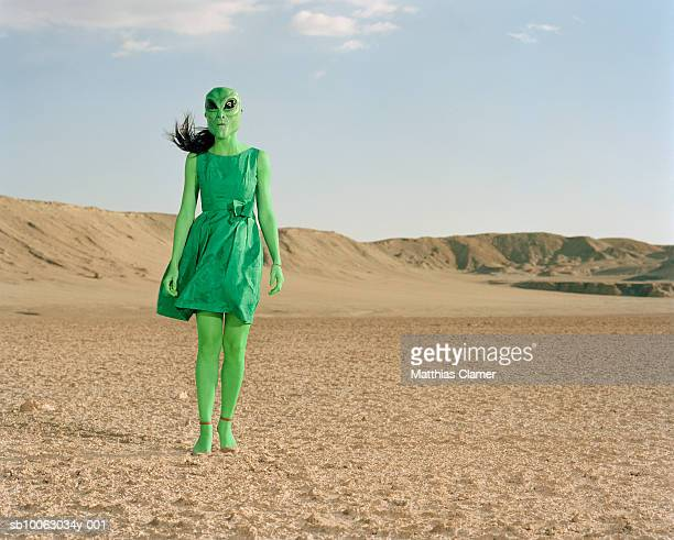 extraterrestrial wearing green dress standing in desert - alien stock-fotos und bilder