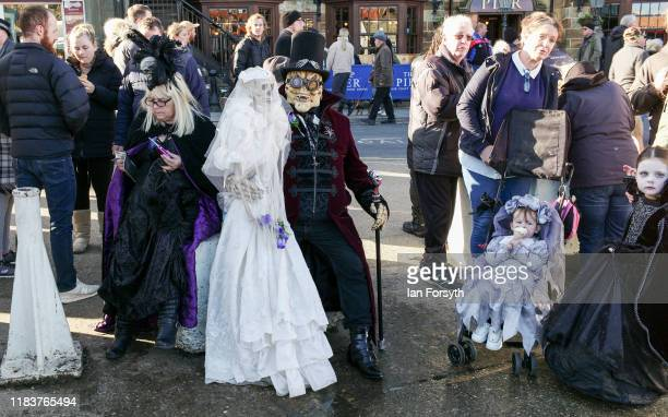 Extravagantly dressed Goths sit outside a food stall during Whitby Goth Weekend on October 27, 2019 in Whitby, England. The Whitby Goth weekend began...