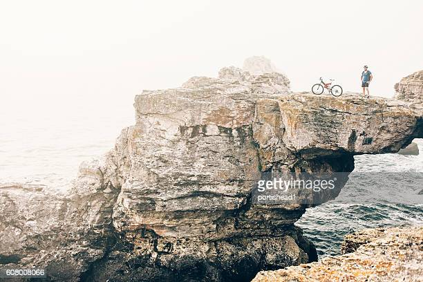 Extreme biker standing on top of the cliff