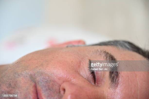 extreme close up of mature adult man sleeping in bed - rafael ben ari imagens e fotografias de stock