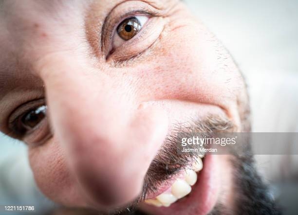 extreme close up portrait of quirky laughing man - extreme close up stock pictures, royalty-free photos & images