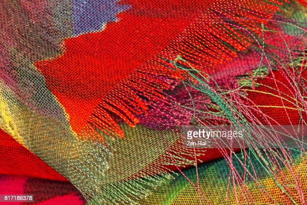 Extreme close-up of a multicolored fabric shows unravelling edges