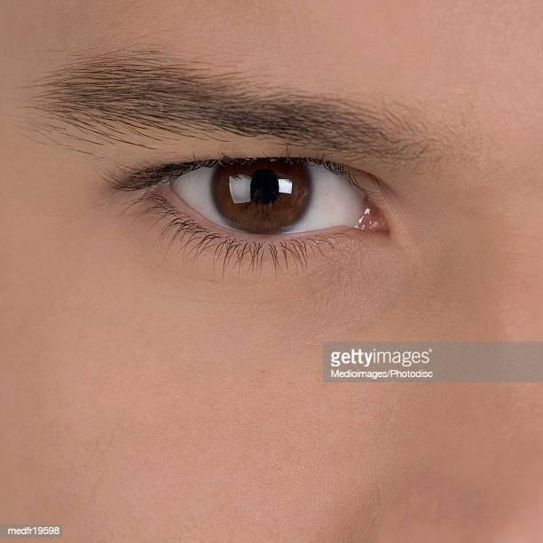 extreme close-up of a young man's eye - bruine ogen stockfoto's en -beelden