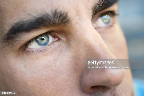extreme close-up of man eye - blue eyes stock pictures, royalty-free photos & images