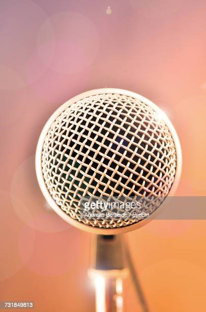 Extreme Close-Up Of Microphone Against Colored Background