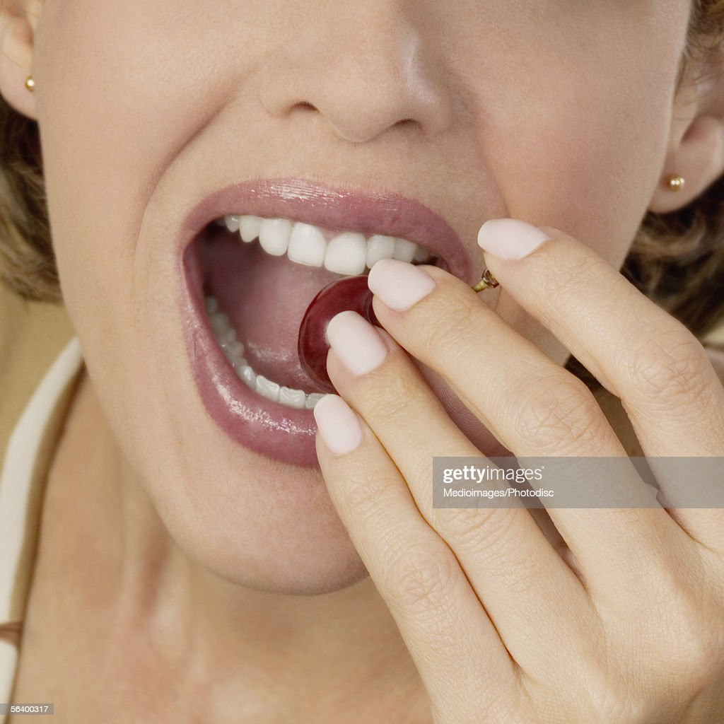 Extreme close-up of mid adult woman eating a cherry : Stock Photo