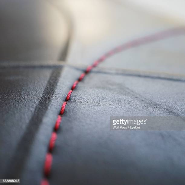 extreme close-up of red stitching on leather bag - stitching stock photos and pictures