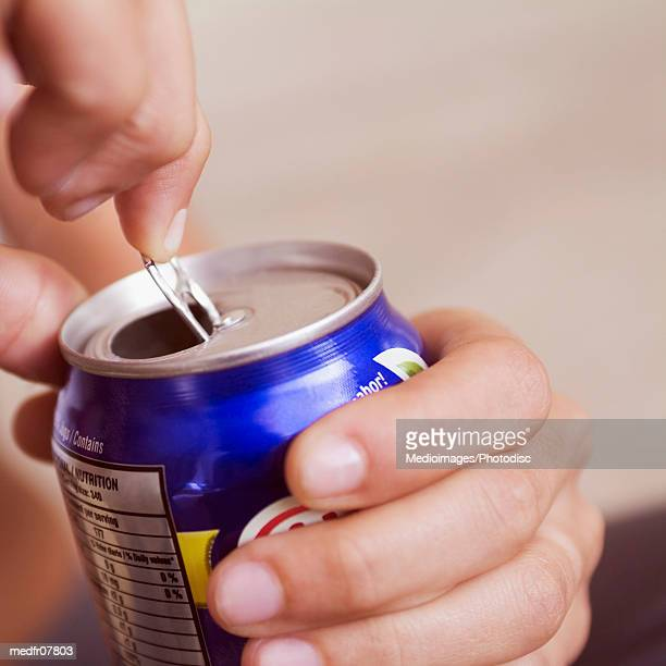 Extreme close-up of woman opening canned drink