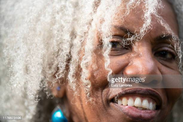 extreme close-up portrait of a beautiful senior woman outdoors - コイリーヘア ストックフォトと画像