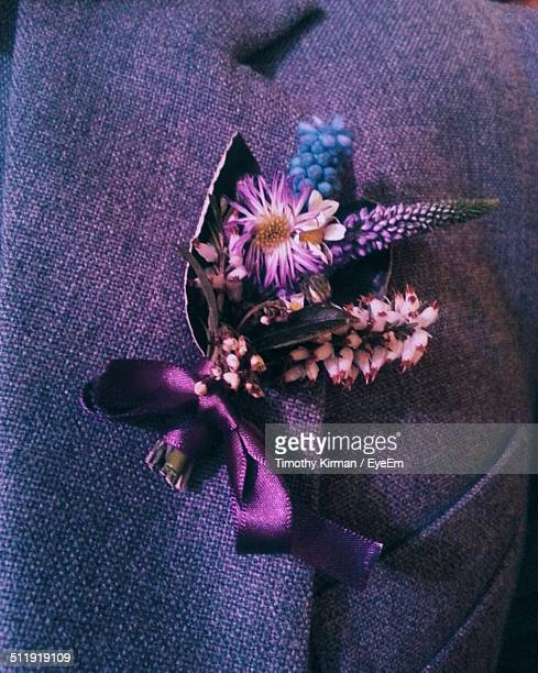 Extreme close-up shot of flower attached on men suit