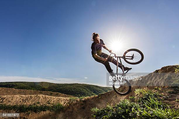 Extreme cyclist practicing on dirt road against the sky.